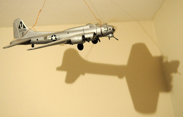 A B-17 model casts a shadow on the wall inside Chester Jech's room at Country Woods Assisted Living Thursday in Kingfisher. Jech and his cousin, Robert Jech, are both veterans of World War II. (Staff Photo by BONNIE VCULEK)