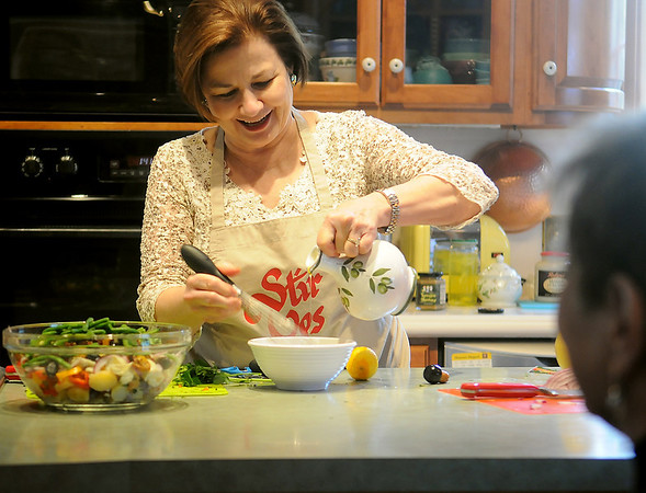 Sherrell Jones prepares an herb dressing for a French potato salad from Cooking by the Boot Straps during the Junior Welfare League of Enid's 9th annual Cookbook Marketplace Thursday at Elmstead. (Staff Photo by BONNIE VCULEK)