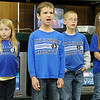Landon Schultz sings a solo as the second grade class from Hillsdale Christian School performs at Hope Outreach Tuesday. (Staff Photo by BONNIE VCULEK)