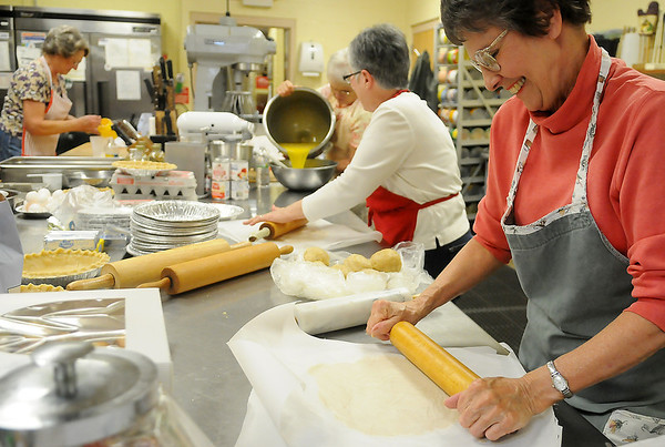 Carolyn Semrad (right) rolls pie crusts with Linda Hubbs Friday as members of the Ladies Auxiliary prepare and bake 65-70 pecan pies and 35 pumpkin pies for their annual fundraising event. (Staff Photo by BONNIE VCULEK)