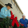 Ton Jerred (left) and Bill Word hang Christmas decorations outside the land office at the Humphrey Heritage Village Wednesday. (Staff Photo by BILLY HEFTON)