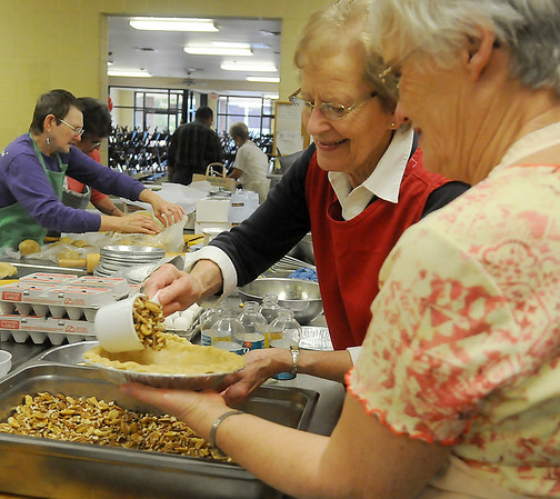 Ladies Auxiliary members form an assembly line as they prepare homemade pecan and pumpkin pies and kolache fillings at Our Daily Bread Friday. (Staff Photo by BONNIE VCULEK)