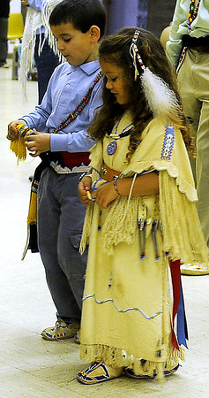 Hagen Childs and Andee Grace Rader participate during the Enid Inter-Tribal Indian Club Gourd Dancing Saturday at the Hoover Building. Rader wears a hand-made buckskin dress and beaded assessories once worn by her grandmother Marie Childs for the first time as she celebrates National Native American Week. (Staff Photo by BONNIE VCULEK)