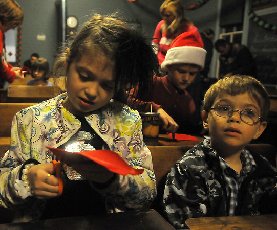 Karissa Burkes (left) and her brother, Haydyn, create a Christmas mouse Friday during Christmas in the Village at the Cherokee Strip Regional Heritage Center Humphrey Heritage Village. (Staff Photo by BONNIE VCULEK)
