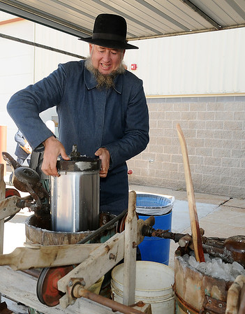 Floyd Schrock, from Chouteau, prepares a large container of homemade ice cream Saturday during the Oklahoma Mennonite Relief Sale. A large cup of the sweet treat costs two dollars for guests during the event that raises funds for Mennonite disaster relief around the world. (Staff Photo by BONNIE VCULEK)