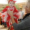 Berlyn Curttright (left) is ready for her first visit with Santa as Shelly Curttright lifts Berlyn from her stroller Friday at Oakwood Mall. Hundreds of children received a bag of treats, milk and cookies during their time with jolly ol' St. Nick. (Staff Photo by BONNIE VCULEK)