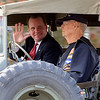 Lt. Gov. Todd Lamb (left) waves to the crowd as United States Marine Corps veteran Arlo Becker drives a military vehicle during the Veterans Day Parade Sunday. (Staff Photo by BONNIE VCULEK)