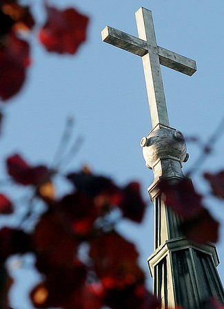 The cross above the entrance to St. Francis Xavier Catholic Church appears above the top of a colorful tree Monday afternoon. (Staff Photo by BONNIE VCULEK)