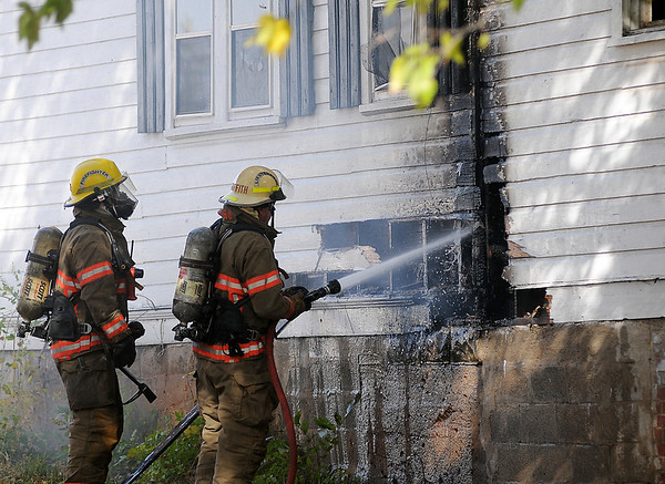 Enid firefighter Adrian Moore and Lt. Rick Griffith battle a house fire at 414 E. Maple Friday. (Staff Photo by BONNIE VCULEK)