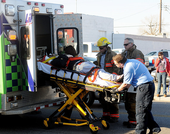 Life EMS and Enid firefighters load a multi-vehicle accident victim into a waiting ambulance Wednesday on W. Maine after a 4-car chain reaction crash. (Staff photo by BONNIE VCULEK)