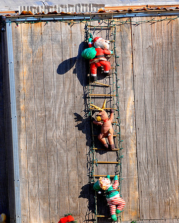 Santa and helpers scale a ladder at a home in Breckinridge. (Staff Photo by BILLY HEFTON)