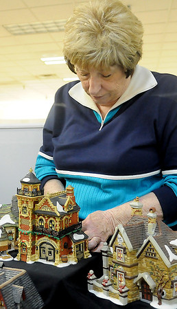 Nancy Jewell positions a light inside the No. 17 Ashwick Lane Hose & Ladder Fire Station Friday as she assists the Enid Arts Council with the set up of more than 300 retired pieces of her collection. The Enid Arts Council, with cooperation from Oakwood Mall and Park Avenue Thrift, will display the unique pieces throughout the holiday in Oakwood Mall. (Staff Photo by BONNIE VCULEK)