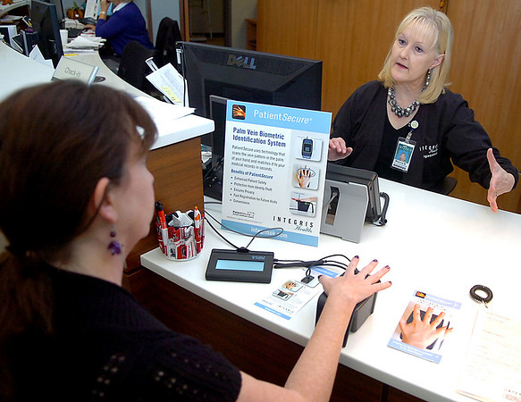 Melonie Stinson, patient acess coordinator at the Integris Heart and Vascular Institute of Northwest Oklahoma, explains the new palm vein biometric identification system being used to identify patients. (Staff Photo by BILLY HEFTON)