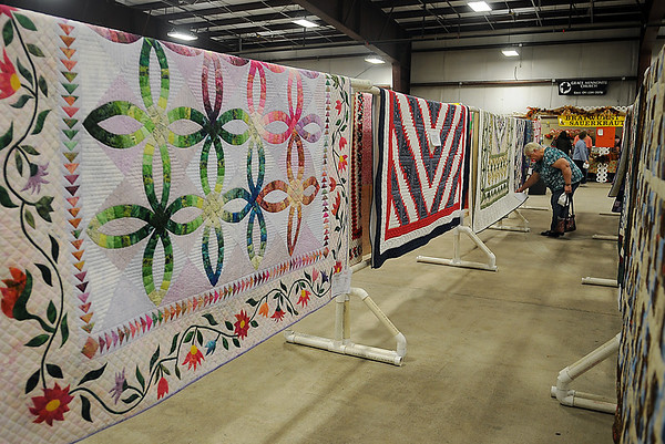 A woman examines one of the handmade quilts available at the 36th annual Oklahoma Mennonite Relief Sale Friday, Nov. 1, 2013. Craft and quilt auctions begin Saturday during the annual disaster relief fundraising event at the Chisholm Trail Expo Center. (Staff Photo by BONNIE VCULEK)