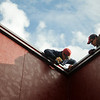 Workers secure accent trim to the roof at the new Pizza Hut in Broadway Plaza Thursday, Nov. 14, 2013. The restaurant is currently hiring employees and will open as soon as renovations are complete. (Staff Photo by BONNIE VCULEK)