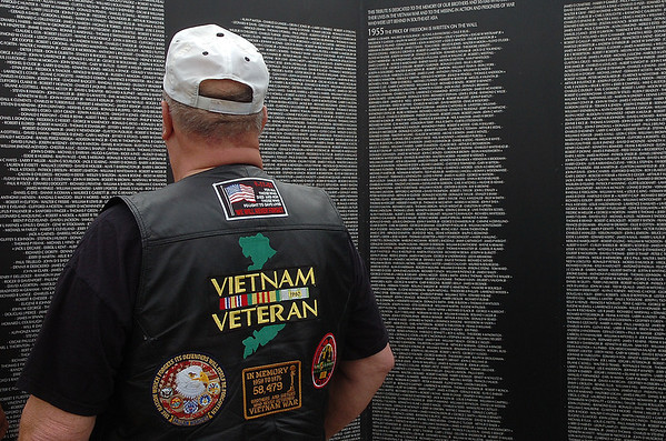 A Vietnam veteran reads the names on a one of the panels of the Vietnam Memorial Wall prior to the start of the retirement and dedication ceremony Monday at Woodring Airport. (Staff Photo by BILLY HEFTON)