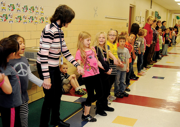 All Monroe Elementary School students and teachers swing their arms as they sing the school song in honor of National Education Week. Ashley Levick, who organized the event, had the 444 Monroe Lions and faculty form a single line around the interior walls, sharing their love that they have for their school. (Staff Photo by BONNIE VCULEK)