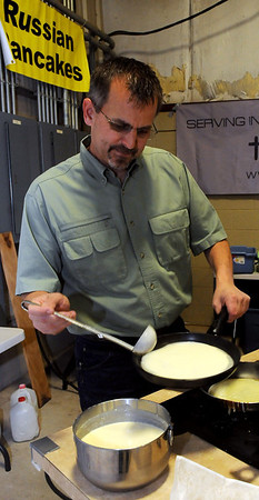Kevin Ediger pours batter into a hot skillet as Memorial Road Mennonite Brethren Church in Edmond prepare Russian pancakes during the Oklahoma Mennonite Relief Sale at the Chisholm Trail Expo Center Saturday, Nov. 2, 2013. Proceeds from the event provide disaster relief around the world. (Staff Photo by BONNIE VCULEK)