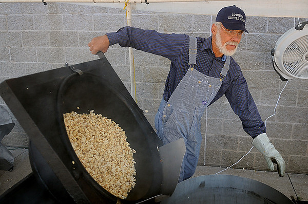 Harvey Jantz empties freshly popped kettle corn into a large container during the 36th annual Oklahoma Mennonite Relief Sale at the Chisholm Trail Expo Center Saturday, Nov. 2, 2013. Jantz has been preparing the special treat for the disaster relief fundraising event for 13 years. (Staff Photo by BONNIE VCULEK)