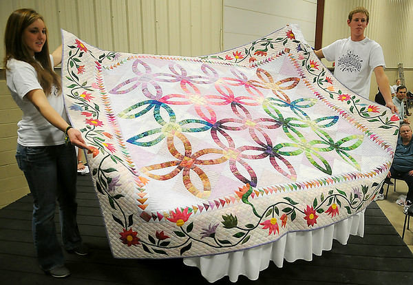 "Rachel Detweiler (left) and Caleb Wichert hold the People's Choice quilt during the Oklahoma Mennonite Relief Sale Quilt and Textile Auction at the Chisholm Trail Expo Center Saturday, Nov. 2, 2013. The 85"" x 96"" pieced, appliqued, hand-made, pastel double wedding ring quilt donated by the First Mennonite Church in Clinton was purchased by Jerry Jantzen and his granddaughter Julia for $2,000. (Staff Photo by BONNIE VCULEK)"