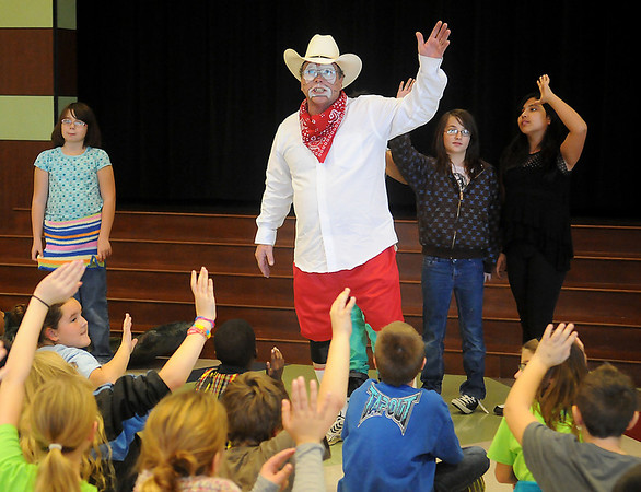 Garfield Elementary School students raise their hands as Marvin Nash, the PBR Bull Riding Rodeo Clown, asks if they have ever been bullied Friday, Nov. 15, 2013. (Staff Photo by BONNIE VCULEK)