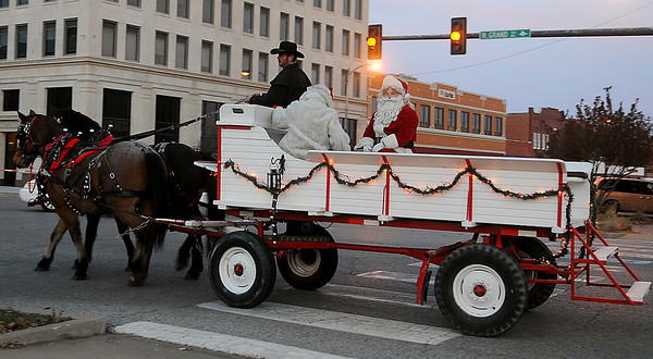 Santa and Mrs. Claus arrive by horse-drawn wagon for Enid Lights Up the Plains in downtown Enid Friday, Nov. 29, 2013. (Staff Photo by BONNIE VCULEK)