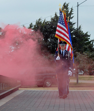Members of the Vance Air Force Base honor guard marches throught the smoke as they present the colors during a retirement and dedication ceremony for the Vietnam Memorial Wall Monday at Woodring Airport. (Staff Photo by BILLY HEFTON)