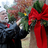 Mike Caffey, maintenance director for the Cherokee Strip Regional Heritage Center, decorates the Humphrey Heritage Village entrances with garland, lights and bows Tuesday, Nov. 19, 2013. Christmas in the Village, sponsored by Humphrey Abstract Company, is a holiday Christmas event that draws over 500 quests each year. Tickets, for $5, are now available for Friday, Dec. 6, 2013, from 5-8 p.m. at the Cherokee Strip Regional Heritage Center's Humphrey Heritage Village. (Staff Photo by BONNIE VCULEK)