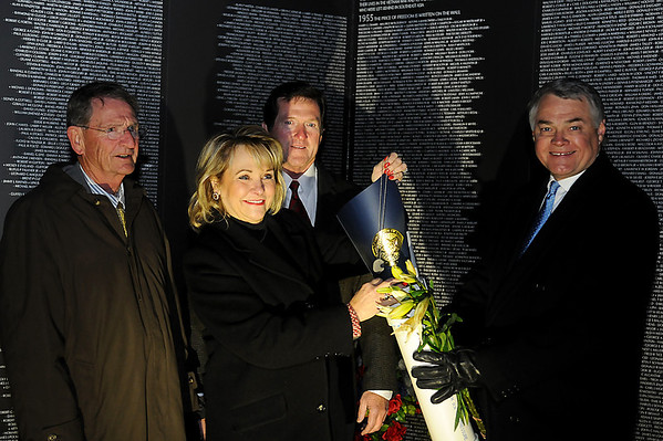 Enid Mayor Bill Shewey, Okla. Gov. Mary Fallin, Wade Christensen and David Henneke (from left) place the Governor's Proclamation and a dog tag into the Vietnam Memorial Wall time capsule Wednesday, Nov. 13, 2013. The time capsule will remain sealed until Nov. 2100. (Staff Photo by BONNIE VCULEK)