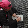 A woman makes an etching of a name following a retirement and dedication ceremony for the Vietnam Memorial Wall Monday at Woodring Airport. (Staff Photo by BILLY HEFTON)