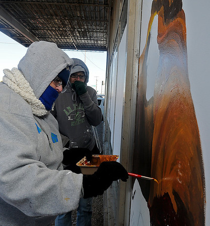 Kera Sleight (back, center) warms her hands as Denecia Mace, from Enid, paints a Christmas mural on the windows of Hope Outreach Ministries Thrift Store Tuesday, Nov. 12, 2013. Mace, an artist for more than 24 years, and Speight braved freezing temperatures throughout the morning as the wind chill dipped to 16. (Staff Photo by BONNIE VCULEK)
