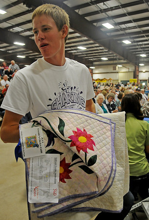 Bidders wait as Caleb Wichert brings the People's Choice quilt to the auction stage during the 36th annual Oklahoma Mennonite Relief Sale at the Chisholm Trail Expo Center Saturday, Nov. 2, 2013. Proceeds raised during the event support disaster relief around the world. (Staff Photo by BONNIE VCULEK)