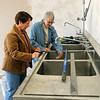 Carol Dockins (left) and Paula Nightengale admire the stainless steel sinks that have been installed inside the new Creative Arts Enid location at 222 E. Maple. Dockins, the administrative director, and Nightengale, chairman of the board of directors for Creative Arts Enid, announced a fundraising event prior to the official opening on Dec. 1. (Staff Photo by BONNIE VCULEK)