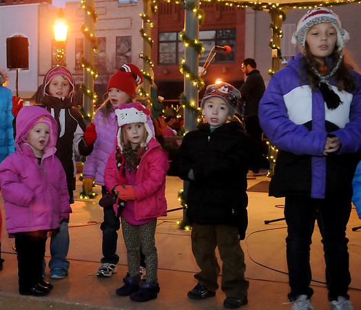 Children sing Christmas carols during Enid Lights Up the Plains Friday, Nov. 29, 2013. Thousands gathered downtown for the 19th annual event. Live music, cash drawings, food, horse-drawn wagon rides, a visit with Santa and Mrs. Claus and the fireworks welcomed the Black Friday guests.  (Staff Photo by BONNIE VCULEK)