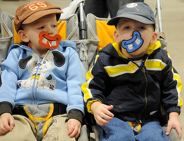 Twins, Ethan and Isaac Walker (from left), sport silly face lollipop holders from Red Dirt Kids & The Cow Poke Cafe during the Officers' Spouses' Club Holiday Marketplace at the Chisholm Trail Pavilion Saturday, Nov. 9, 2013. Kellie Walker, the twins' grandmother, creates and assembles several hand made items for children in a smoke free shop. (Staff Photo by BONNIE VCULEK)