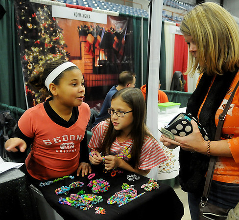 Kaelyn Ford (left) and Kiera Peters sell their rubberband jewelry during Home for the Holidays Home Show at the Chisholm Trail Expo Center Saturday, Nov. 23, 2013. (Staff Photo by BONNIE VCULEK)