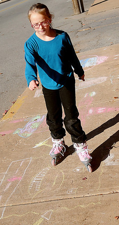 Chaulk art appears below Erin Traynor as she tries out her new roller blades Saturday, Nov. 30, 2013. Traynor created the artistic drawings during Enid Lights Up the Plains Friday. (Staff Photo by BONNIE VCULEK)