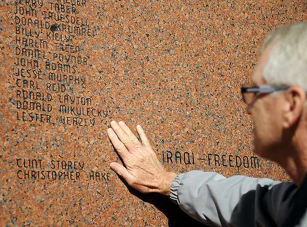 Ken Parker touches the back of the Veterans of Foreign Wars Memorial at Government Springs Park Thursday, Nov. 7, 2013, after the name of Lester Veazey, his half-brother, was etched into the Vietnam Veterans section. Veazey was critically wounded during the attack on Hill 881, and died at the age of 29 in 1977. The memorial, sponsored by the Veterans of Foreign Wars Lodge No. 2270 in Enid,  honors all Garfield County residents who were wounded or killed in the line of duty since World War I. (Staff Photo by BONNIE VCULEK)