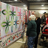 Guests at the 36th annual Oklahoma Mennonite Relief Sale view the People's Choice quilt (left) at the Chisholm Trail Expo Center Saturday, Nov. 2, 2013. (Staff Photo by BONNIE VCULEK)