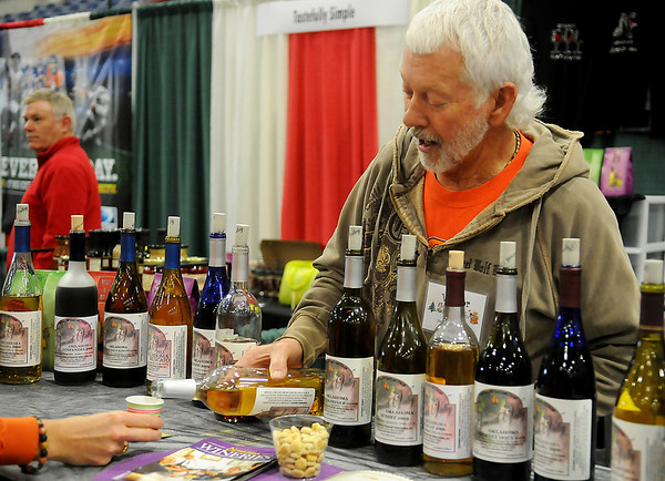 Dennis Flaming, with Plymouth Valley Whinery, pours a sample for a client during the Home for the Holidays Home Show at the Chisholm Trail Expo Center Saturday, Nov. 23, 2013. (Staff Photo by BONNIE VCULEK)