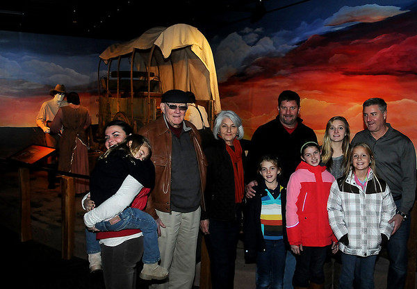 Gigoux family (from left) Victoria, Ainsley, Jim, Mary Jane, Elena, Gerald, Bella, Avery, Juliette and Jeffrey pause near the covered wagon Tuesday, Nov. 26, 2013, donated to the Cherokee Strip Regional Heritage Center in 1977 by their family. Jim Gigoux (third from left) and his wife, Mary Jane, invited their two sons, Gerald and Jeffrey and their families to Enid during Thanksgiving so the group could view part of their family's heritage. (Staff Photo by BONNIE VCULEK)