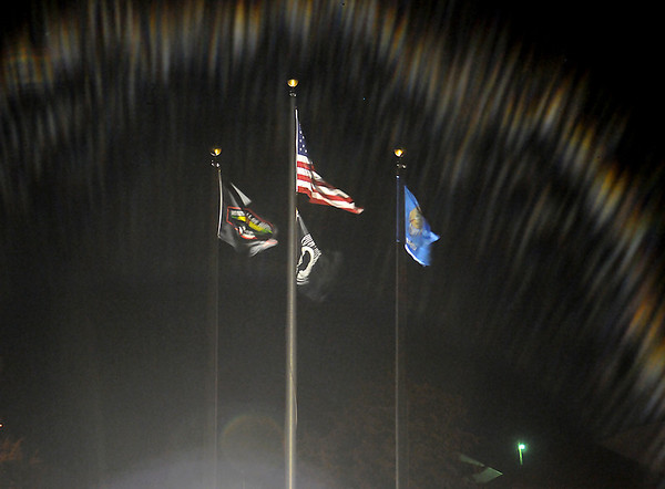 Reflecting streaks of light cast a glow on the Vietnam Memorial Wall flags at Enid Woodring Regional Airport Wednesday, Nov. 13, 2013. (Staff Photo by BONNIE VCULEK)