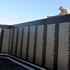 Seregio Moralez, from Bass Construction, puts the finishing touches on the granite cap at the Vietnam Memorial Wall Thursday, Nov. 7, 2013. The dedication of the retired traveling exhibit at Enid Woodring Regional Airport will be at 11 a.m. on Veterans Day, Monday, Nov. 11, 2013. (Staff Photo by BONNIE VCULEK)