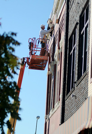 Eric Ingram, from Standard Builders of Enid, repairs the trim on the Old Masonic Temple, AD. 1900. AL.5900, at the corner of Independence and Maine Thursday, Nov. 7, 2013. (Staff Photo by BONNIE VCULEK)