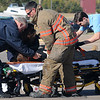 First responders from Life EMS and the Enid Fire Department assist a woman injured in a two-vehicle accident at the N. Van Buren and Mulberry intersection near Burger King Friday, Nov. 1, 2013. Life EMS transported the woman to a nearby hospital as Enid Police detoured traffic around the collision area during their investigation. (Staff Photo by BONNIE VCULEK)