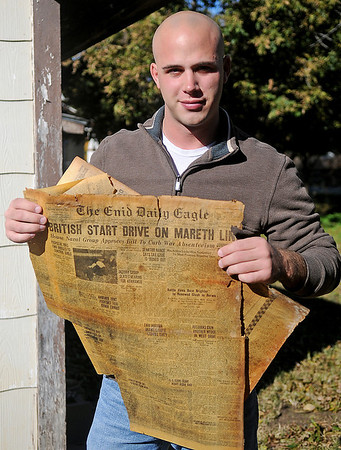 Brian Schwarzkopf holds a March 17, 1943 edition of The Enid Daily Eagle at his home on N. Taylor Saturday, Nov. 9, 2013. Schwarzkopf discovered the newspaper while renovating flooring at his residence. (Staff Photo by BONNIE VCULEK)
