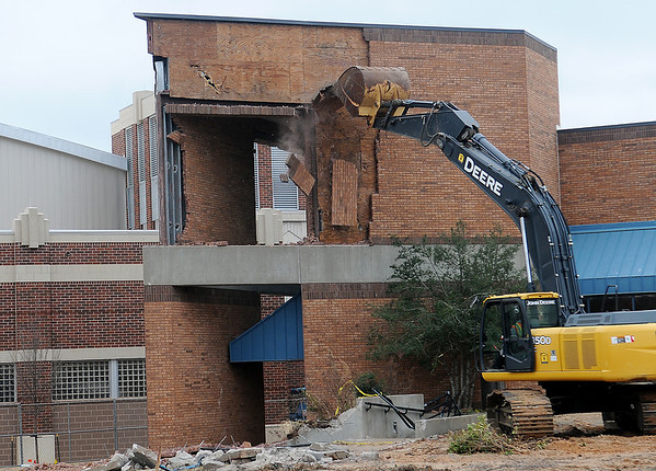 Large sections of brick fall from the northeast corner of the Cherokee Strip Conference Center as an employee with American Demolition and Site Services, LLC uses an excavator Friday, Nov. 22, 2013. Demolition of the conference center and the Kress Building will make way for the new downtown Enid hotel. (Staff Photo by BONNIE VCULEK)