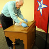 Bill Nokes, a volunteer at the Cherokee Strip Regional Heritage Center, places a gavel on the top of an old desk that was used at the 1907 Oklahoma State Convention. The desk, used by A.H. Ellis, will be on display this Saturday. (Staff Photo by BONNIE VCULEK)