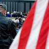 A veteran bows his head during a retirement and dedication ceremony for the Vietnam Memorial Wall Monday at Woodring Airport. (Staff Photo by BILLY HEFTON)