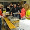 Volunteers assemble Thanksgiving Day dinners for individuals and families that did not have transportation to St. Francis Xavier Catholic Church Leven Center Thursday, Nov. 28, 2013. Leroy and Al Patocka, with The Knights of Columbus Lodge 1044, organized the volunteers and prepared 380 pounds of turkey with dressing, gravy, mashed potatoes, green beans, corn, salad, dinner rolls, pie or cake. More than 450 guests enjoyed the free meal during the holiday. (Staff Photo by BONNIE VCULEK)